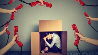 stressed-young-business-woman-sitting-hiding-in-a-box-overwhelmed-by-picture-id855837024