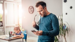 Worried father looking at smart phone