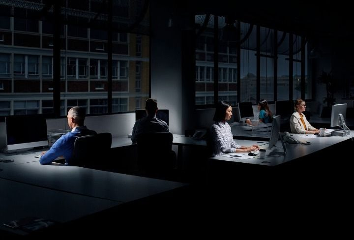 employees-using-computers-in-dark-office-picture-id557608477