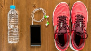 bottle-of-water-telephone-and-running-shoes-for-sports-on-a-dark-picture-id683119284 (1)